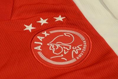 Het logo en de sterren zijn met witte garen op een roodkleurig en rond embleem gestikt. © Ajax Life