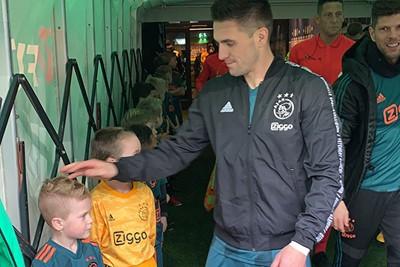 Juist, dan krijg je een aai over de bol van aanvoerder Tadic. © Ajax Kids Club