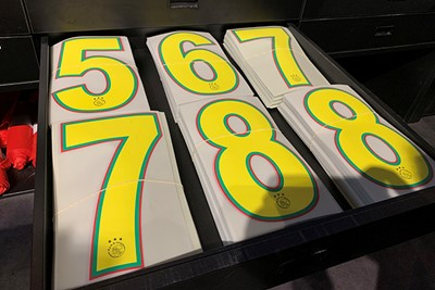 Rugnummers liggen klaar om op shirts te worden geperst. © Ajax Life