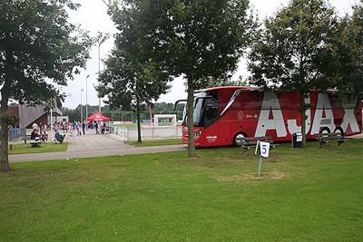 De spelersbus werkt als een magneet op de jeugdige Ajaciedjes. © De Brouwer